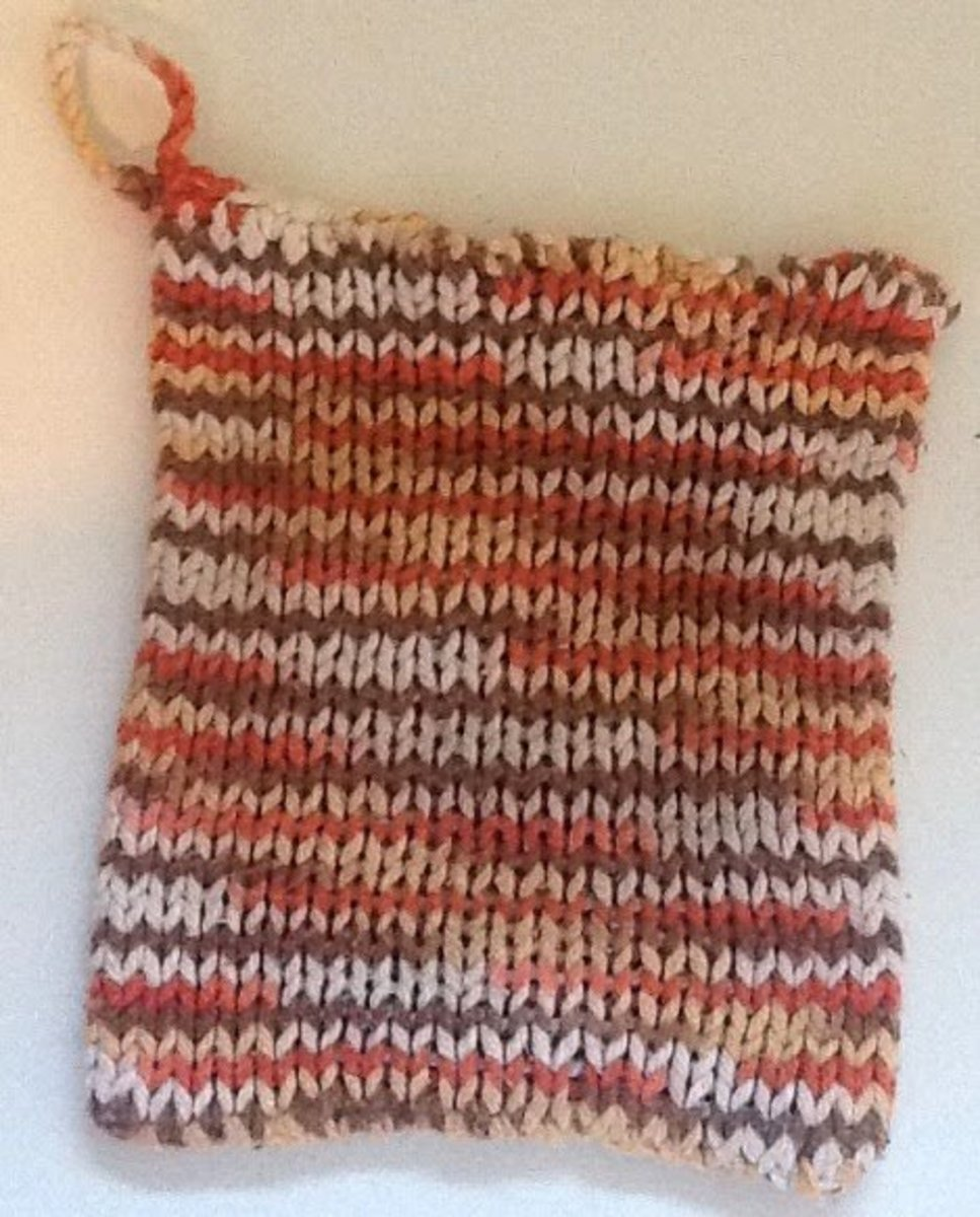 This is a loom knit potholder that is great for beginning knitters. It has a crocheted loop for hanging.