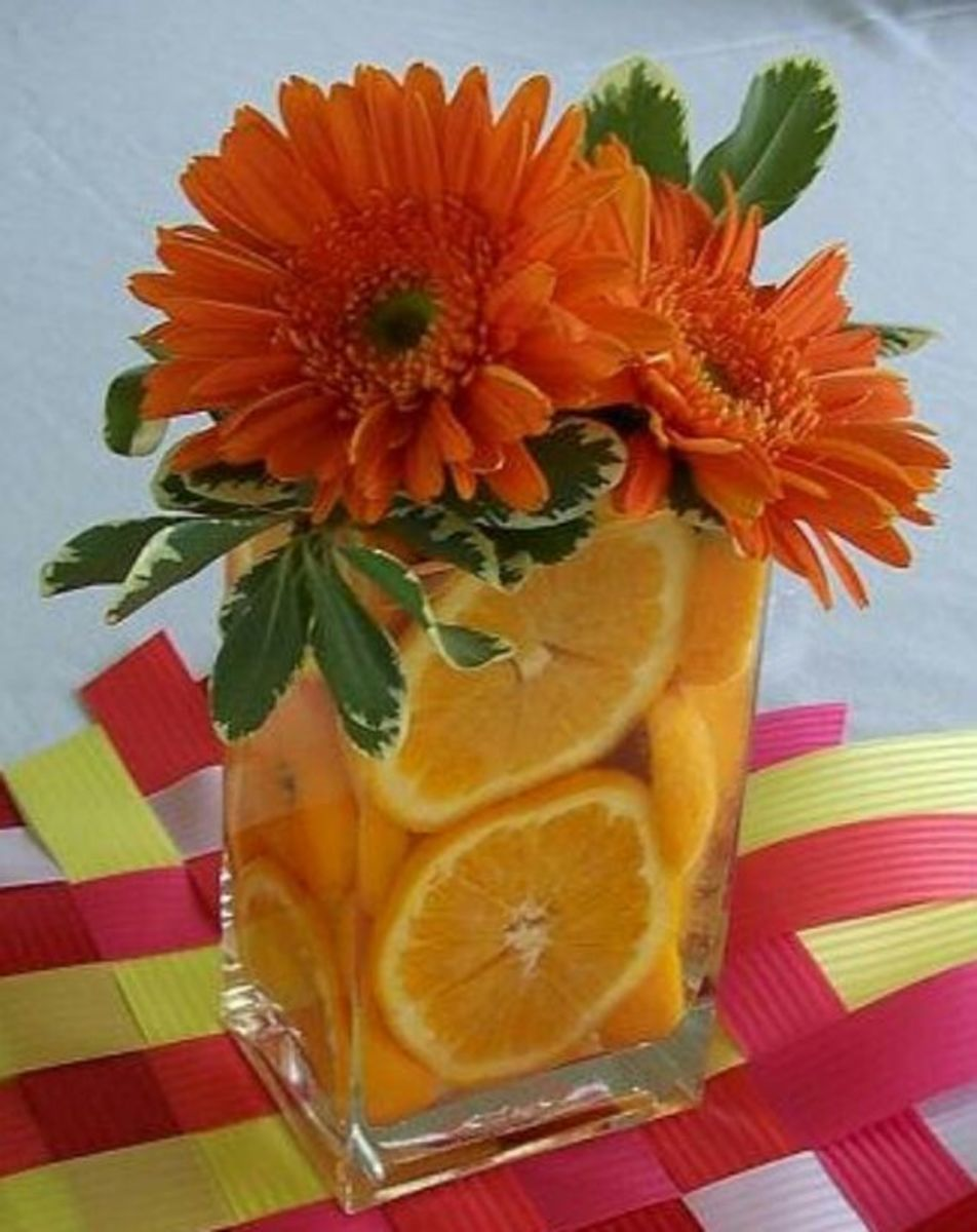 I love the way these gerber daisy's are accented with oranges in a clear rectangular container.