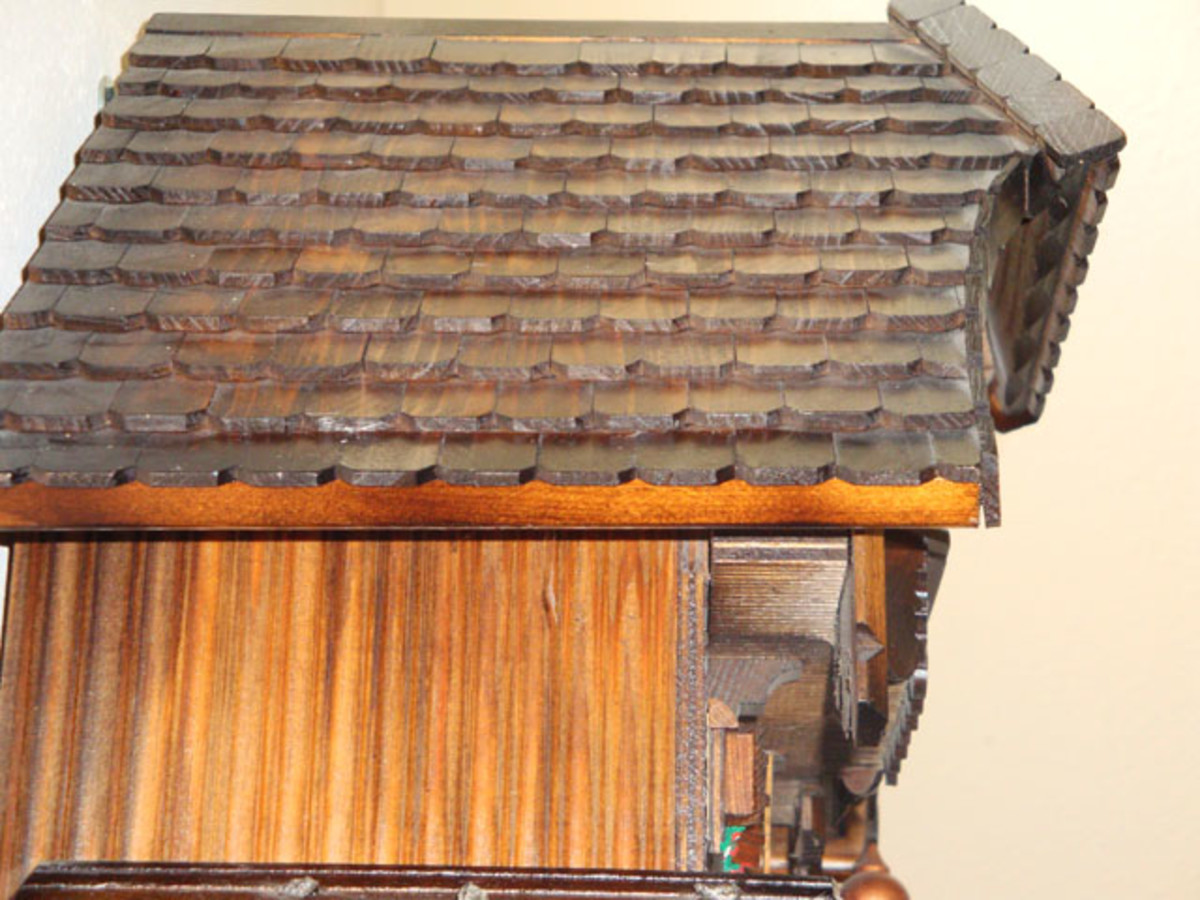 The chalet-style cuckoo clock has a wood shingle roof.