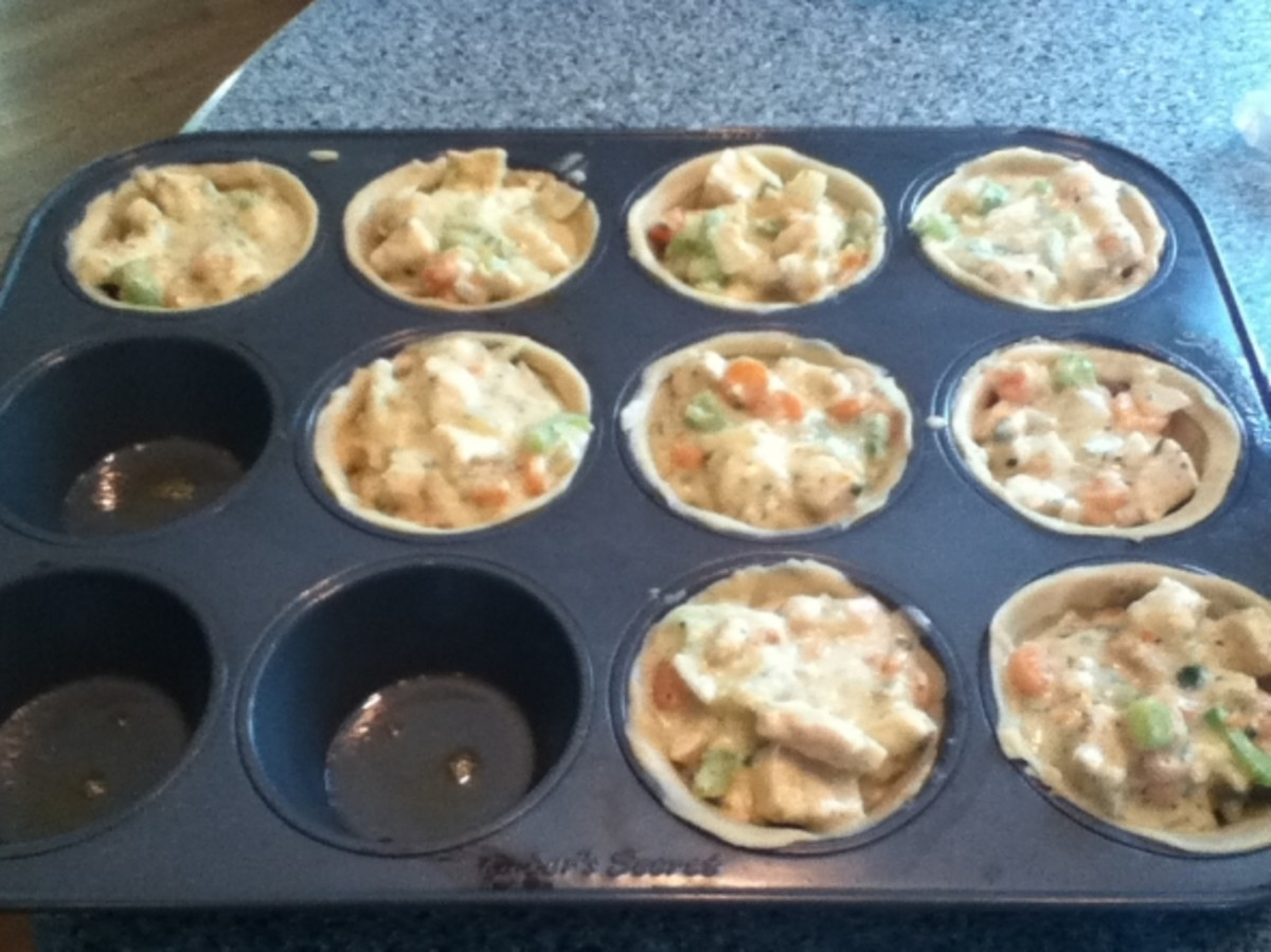 Adding in the chicken mixture to the pastry in the muffin tins