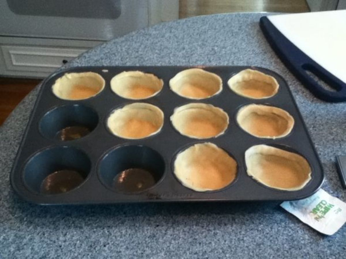 Filling the pan with the pie crust. I tried to stretch it as much as possible to the top of the muffin tin.