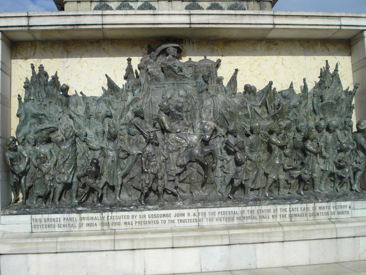 On the side walls of the statue of Queen Victoria