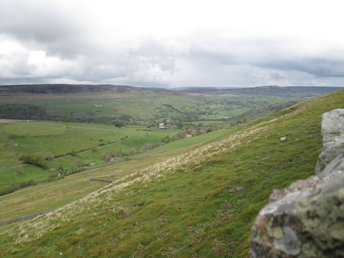High up on the slopes of Swaledale, look back towards Reeth. A narrow road leaves the B6270 west of Reeth and climbs the daleside toward its crest where you can look south into Wensleydale.