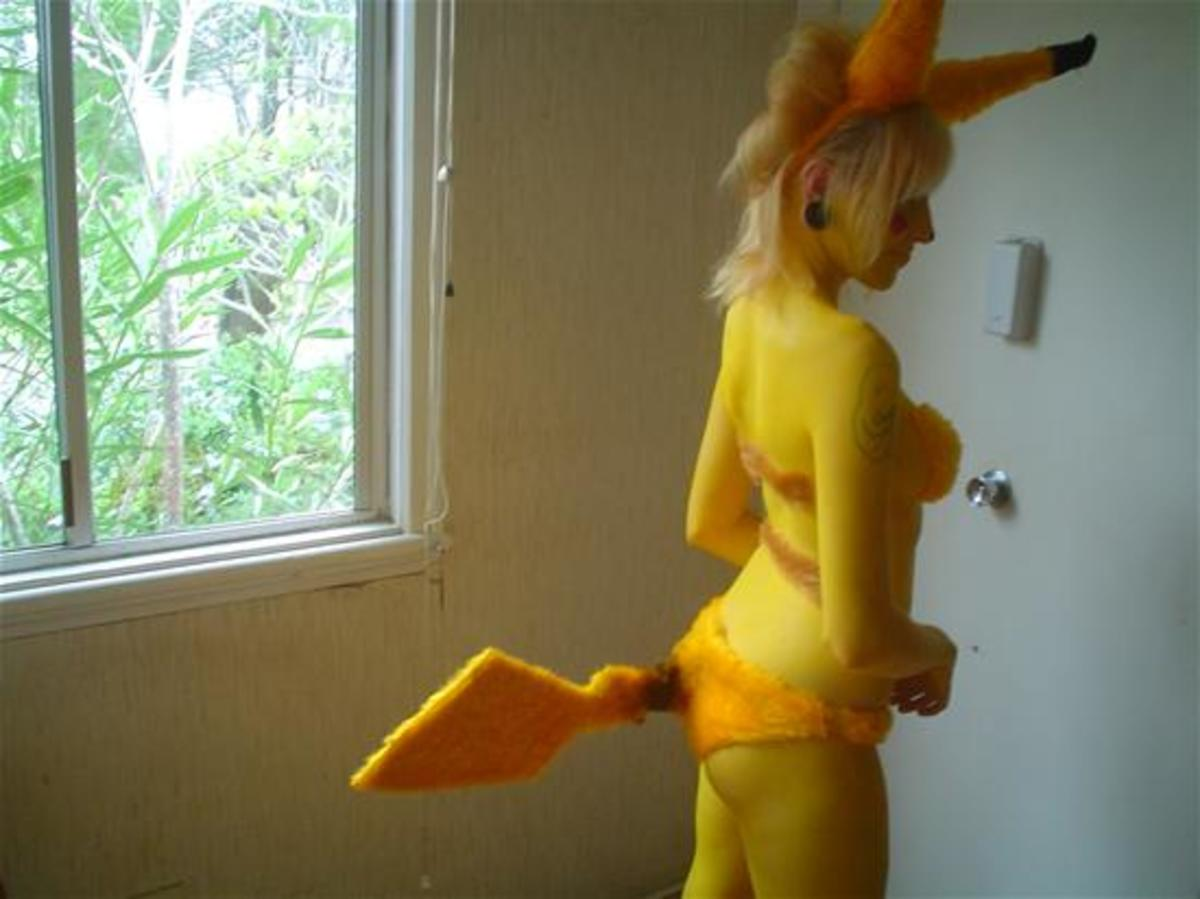Pikachu Girl using a furry set with added tail and ears. She also painted her whole body yellow to look like pikachu.