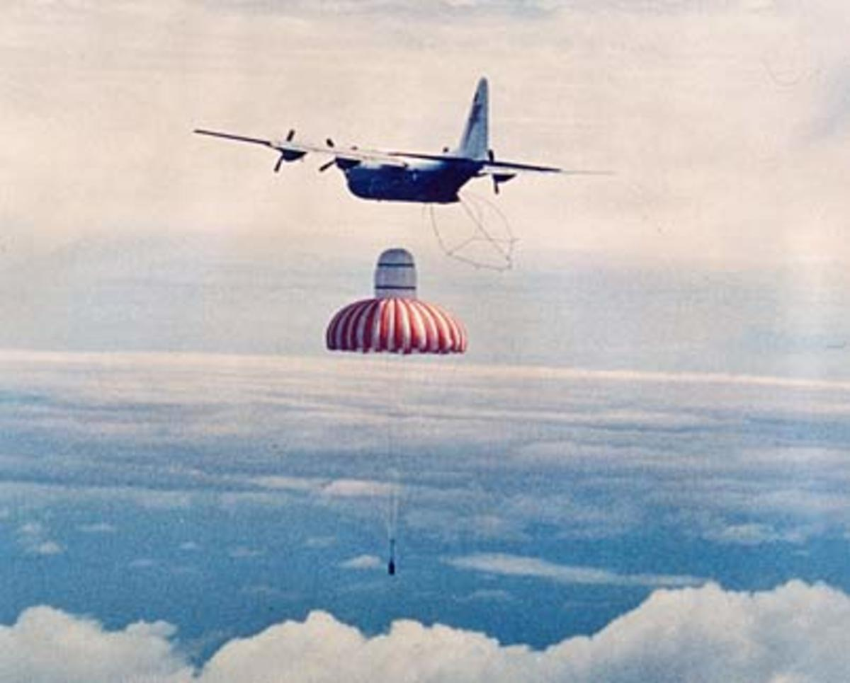 A C-130 Hercules in the process of catching a canister.