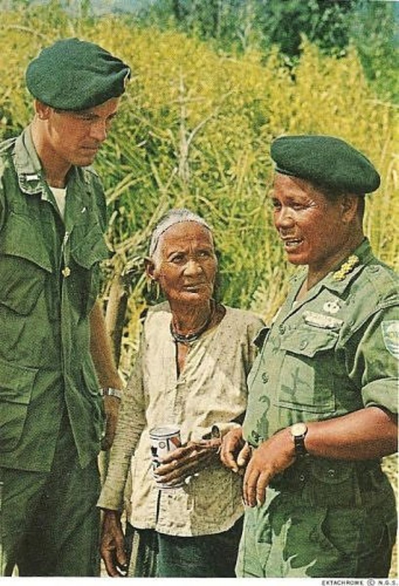 Capt. Do CAo Bo. Montagnard commander of An Lac confers with the camps XO, Lt. Carl Freeman III, and a village matriarch