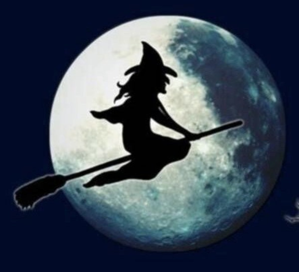 A Halloween witch against the full moon.