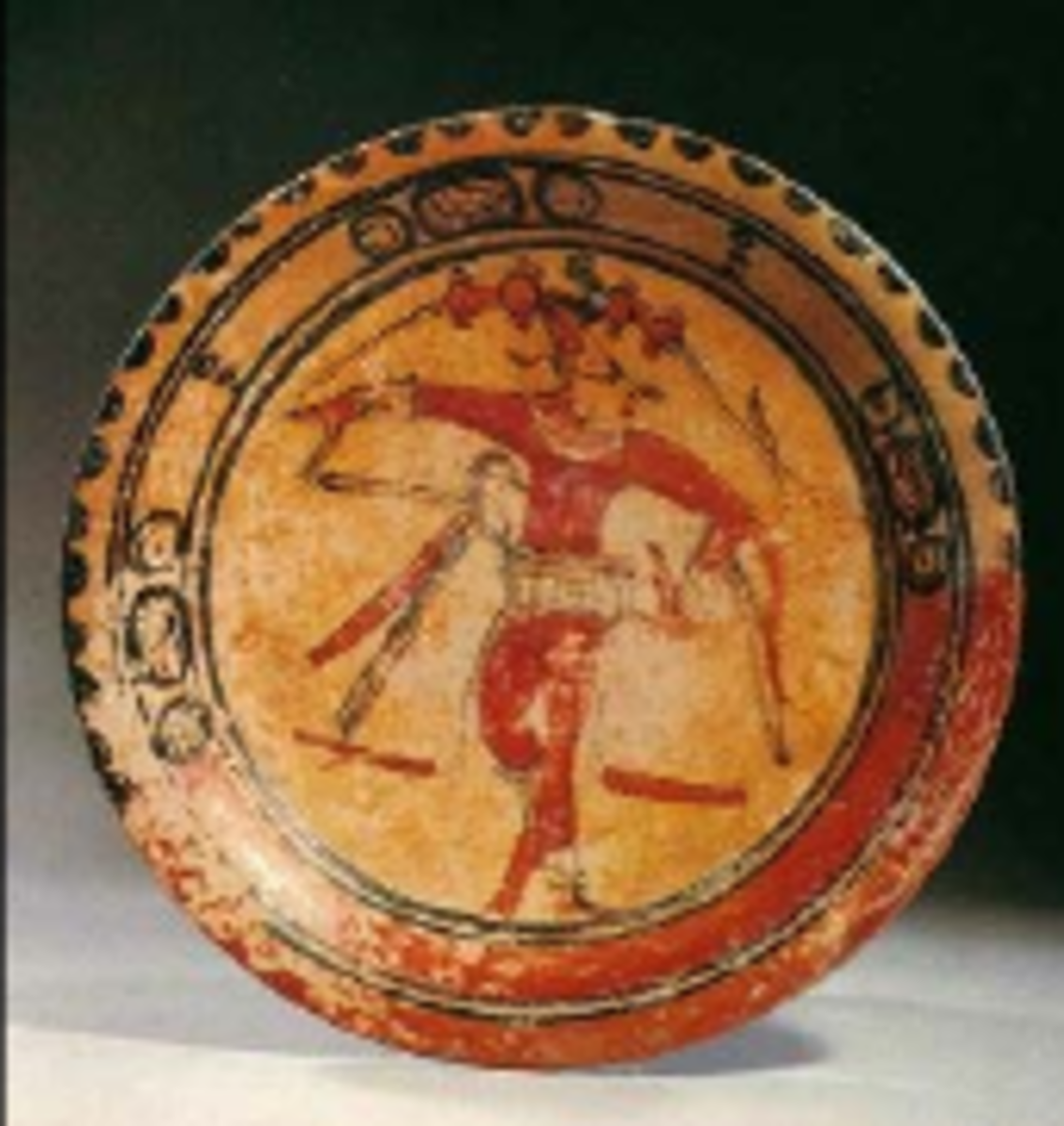 Three hieroglyphic designs circle the central dancing figure on this plate. The dancing Maize God is depicted in a dynamic position. He wears a waist belt known form ball games.