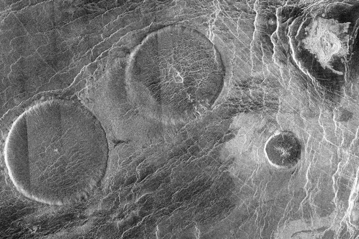 A group of pancake domes called the Carmenta Farra. The largest of these domes is 65 km (40 miles) across and about 1000 m (3200 ft) high. Top right in this photograph is a 12 km (7.5 mile) diameter impact crater known as Margareta