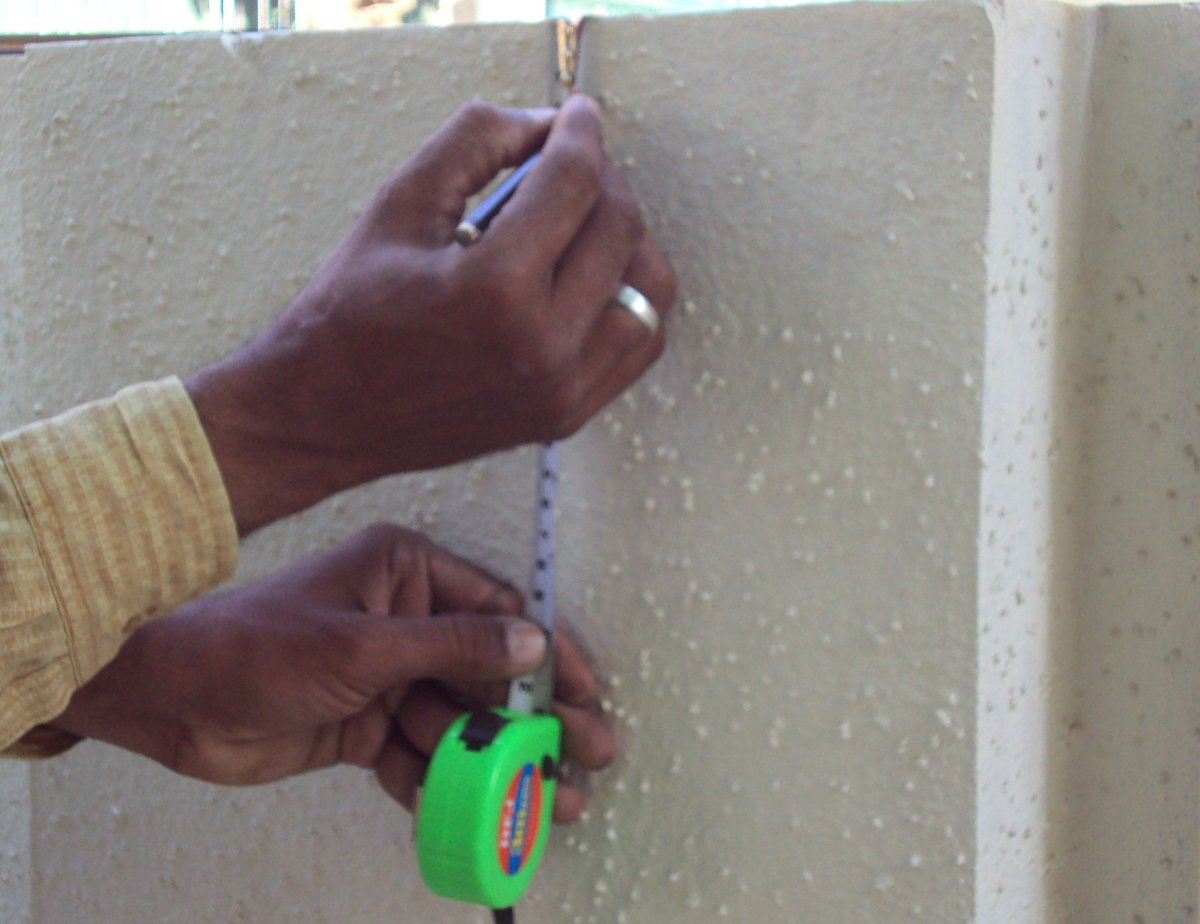 Artist taking primary measurements on the wall