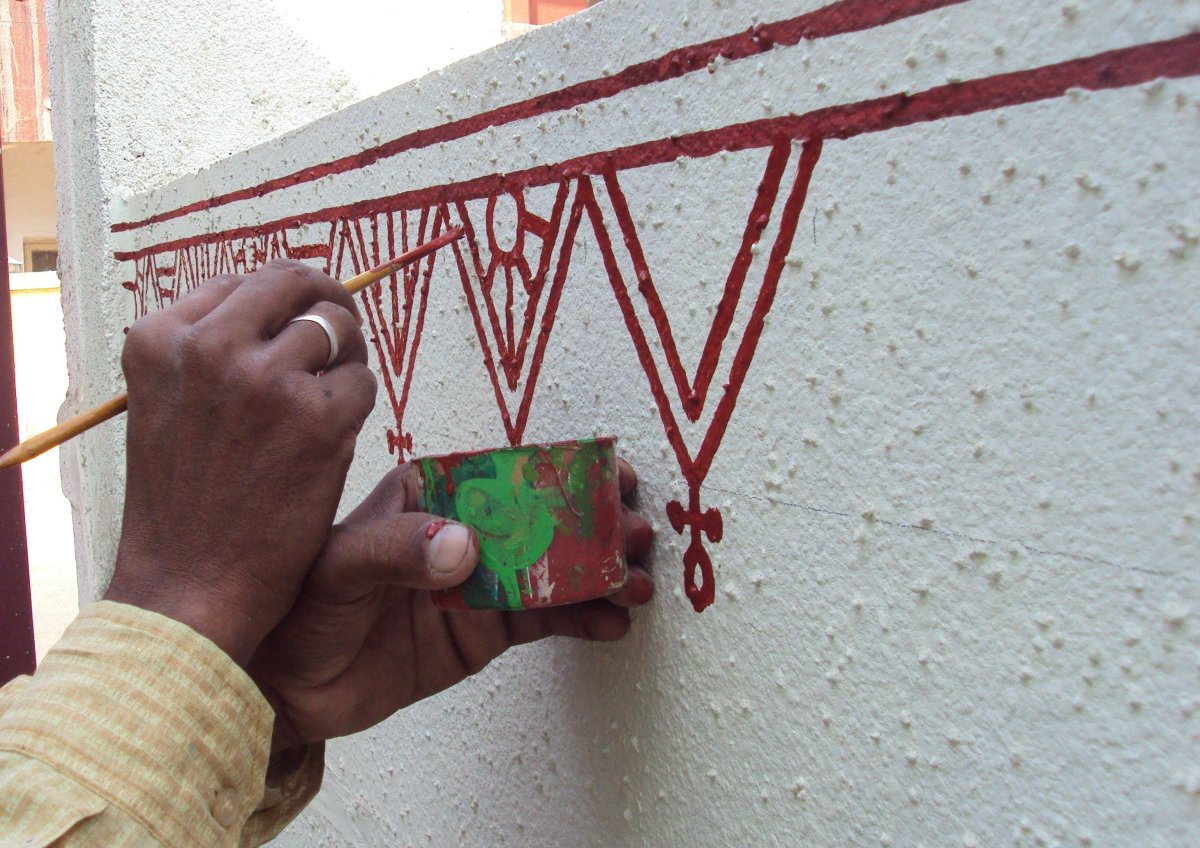 Artist painting triangular border motifs