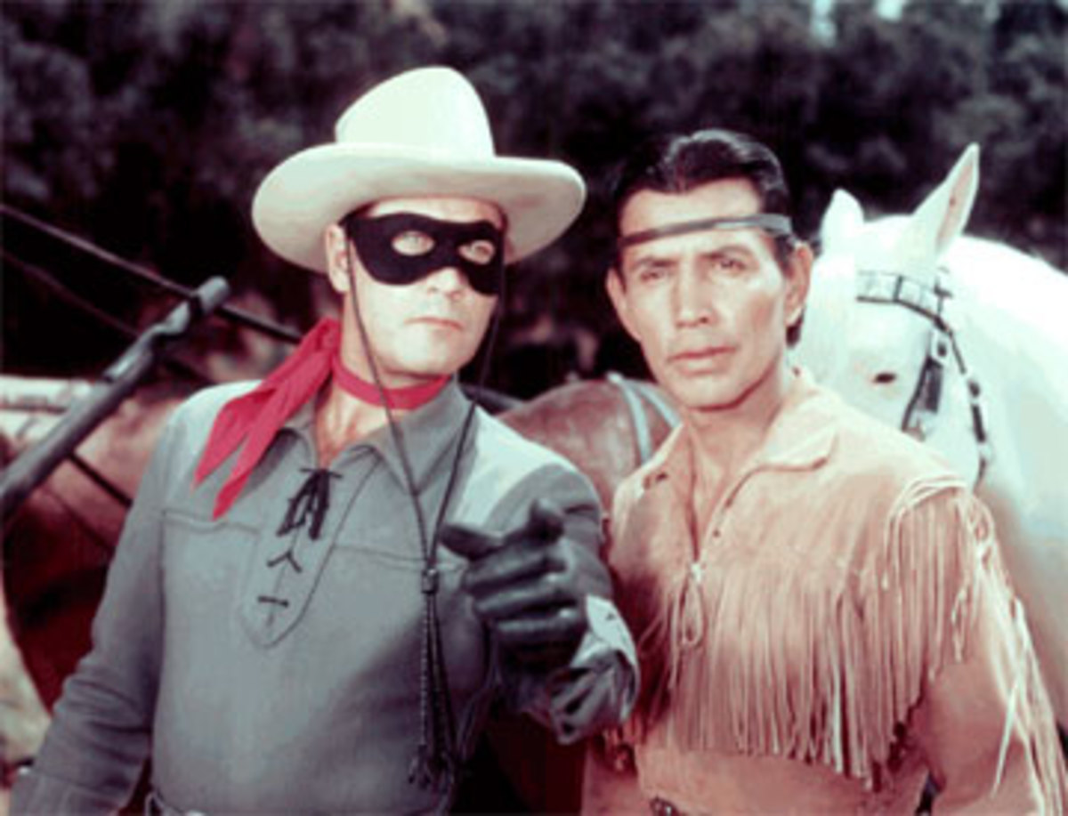The Lone Ranger, left, with Tonto, right, and their horses Scout, lack left, and Silver, back right