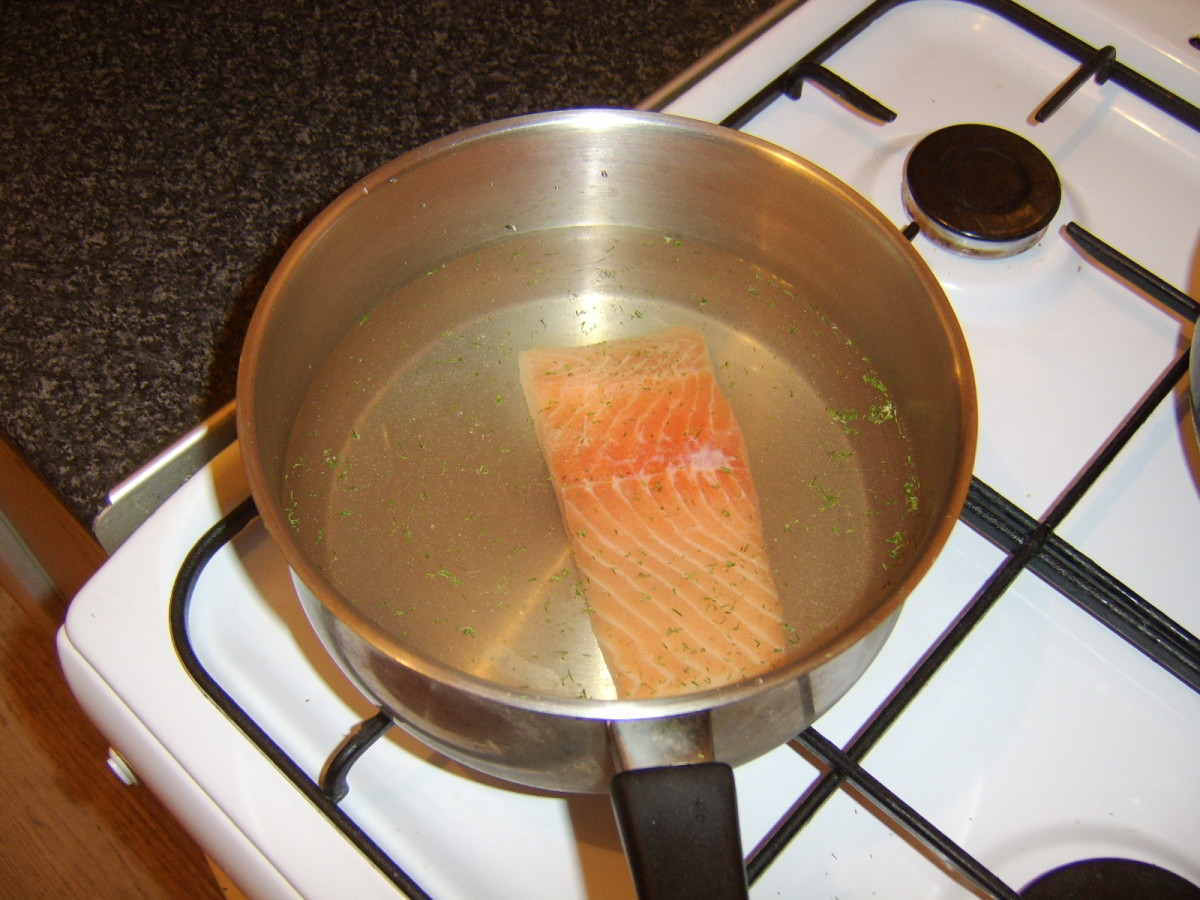 Salmon fillet is seasoned and submerged in diluted white wine