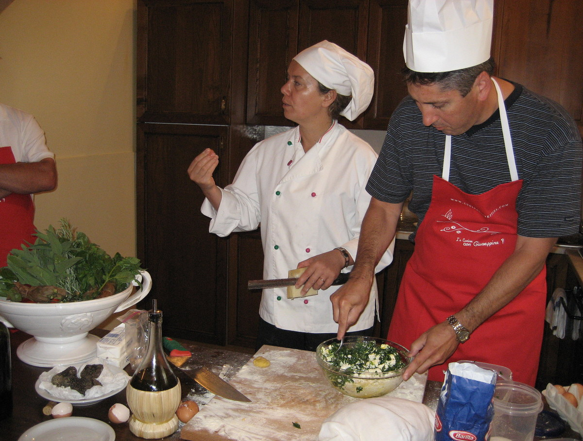 """Chef Giuseppina demonstrates the """"four-finger pinch"""" as a student prepares the ravioli filling"""