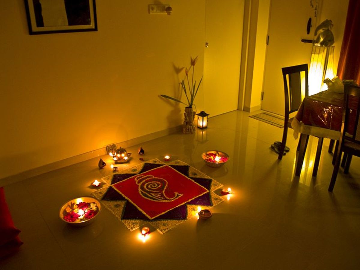 Adorned with oil lamps this design is on the living room floor for Diwali.