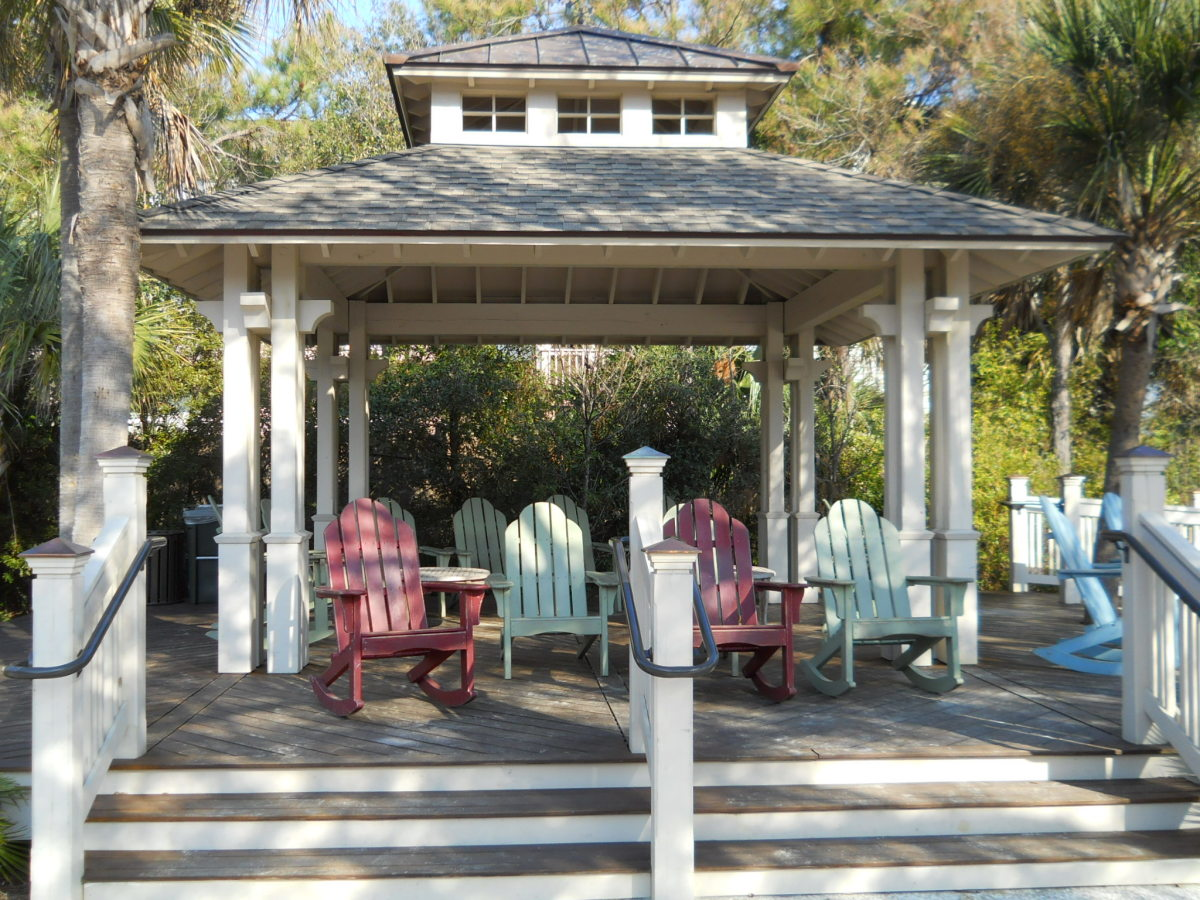 Brightly painted wooden rockers are sheltered from the sun by an open gazebo which overlooks stunning views of the beach and ocean.