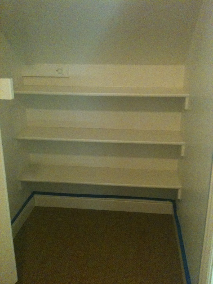 Before - all white shelving in the closet.