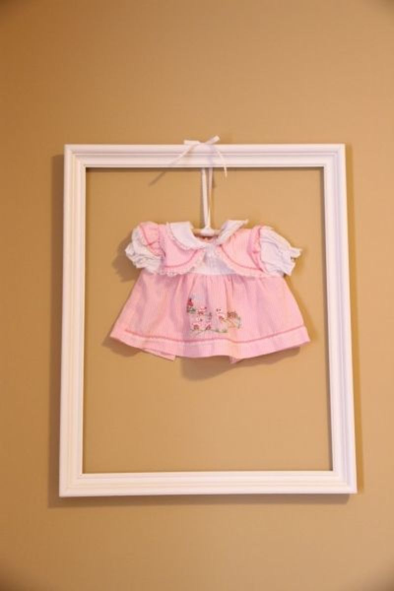 Cut a dowel rod, tie a ribbon, hang a vintage dress from your childhood, paint a picture frame and tack the ribbon on!