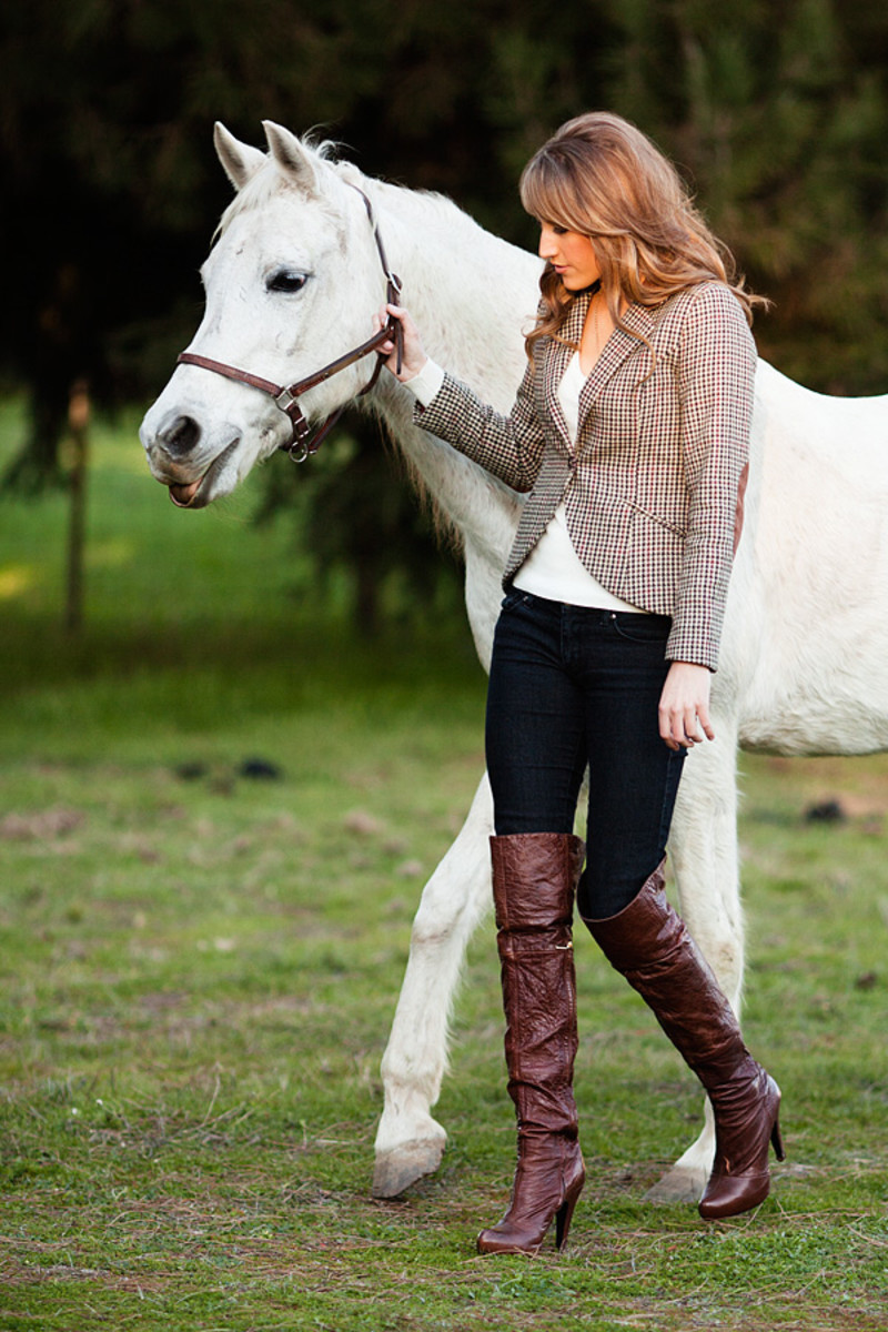 High Fashion Equestrian Style - Beautiful Model in Riding Pants, Boots and Gloves Leading a White Horse