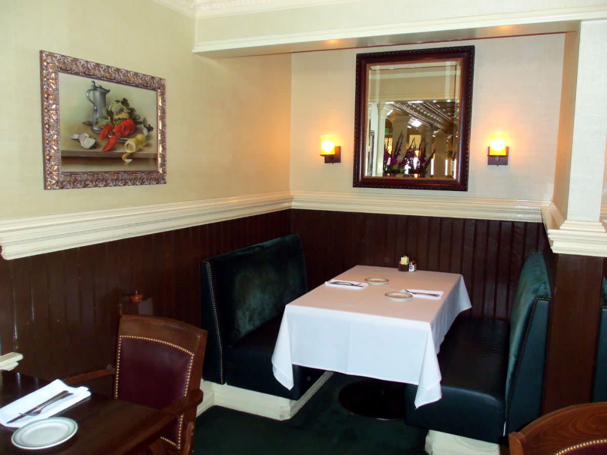 - Typical cozy booth setting situated within the main dining area - Remote enough to enjoy a more intimate dining experience - Hardwood tables, intricate wainscotting, and a variety of portraits on display as accentuating features -