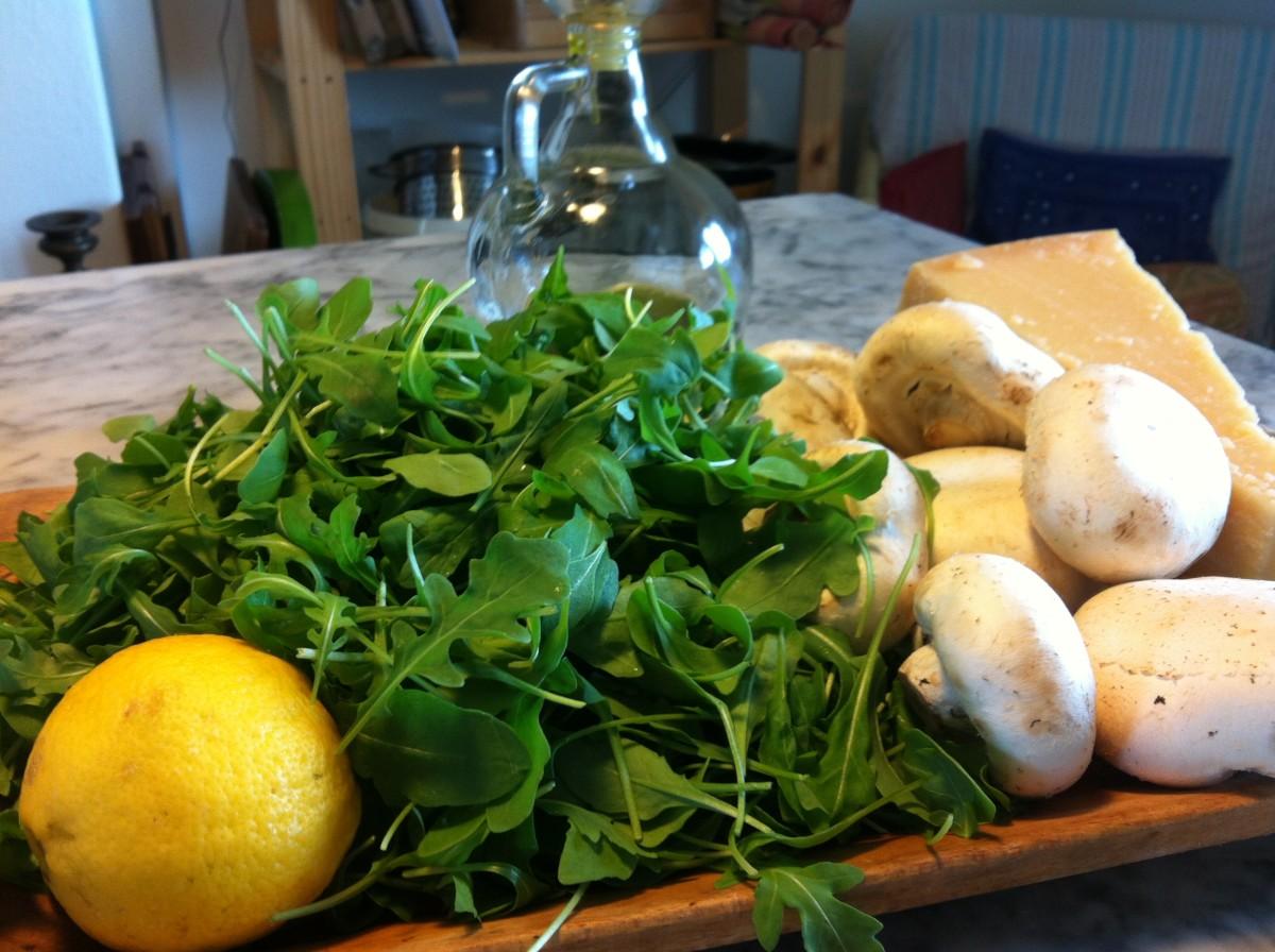 Ingredients arugula, Champignon mushrooms, Parmesan cheese, lemon and olive oil