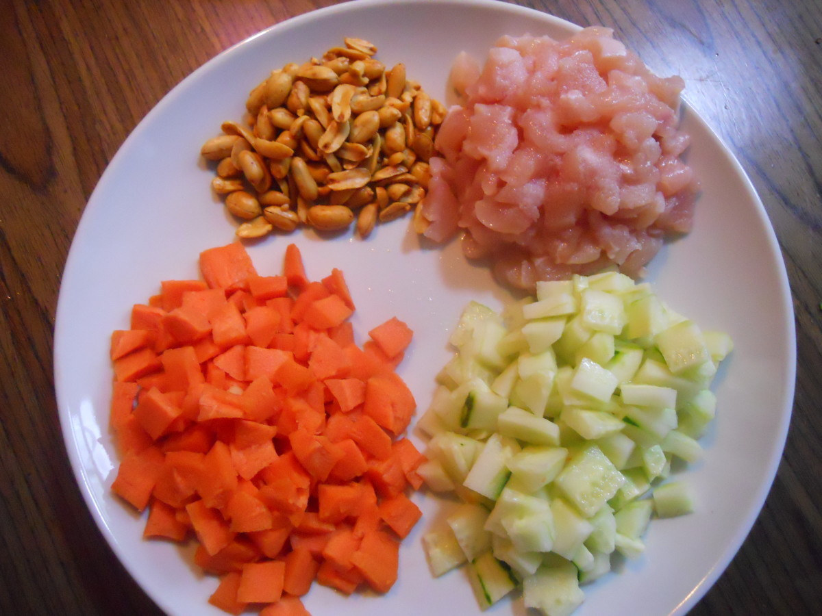 Clockwise; peanuts, chicken, cucumber, and carrots.