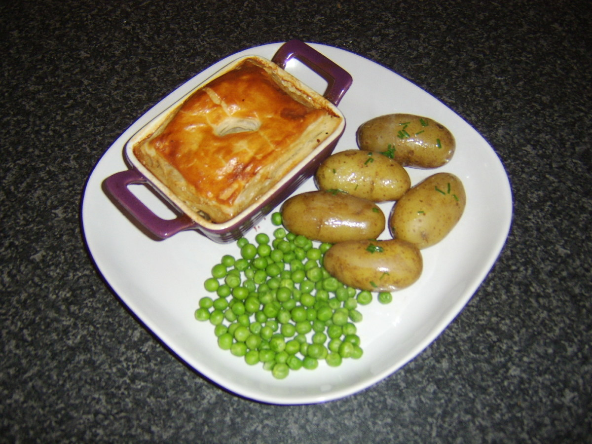 Oxtail and oyster puff pastry pie with chive buttered potatoes and peas is ready to serve