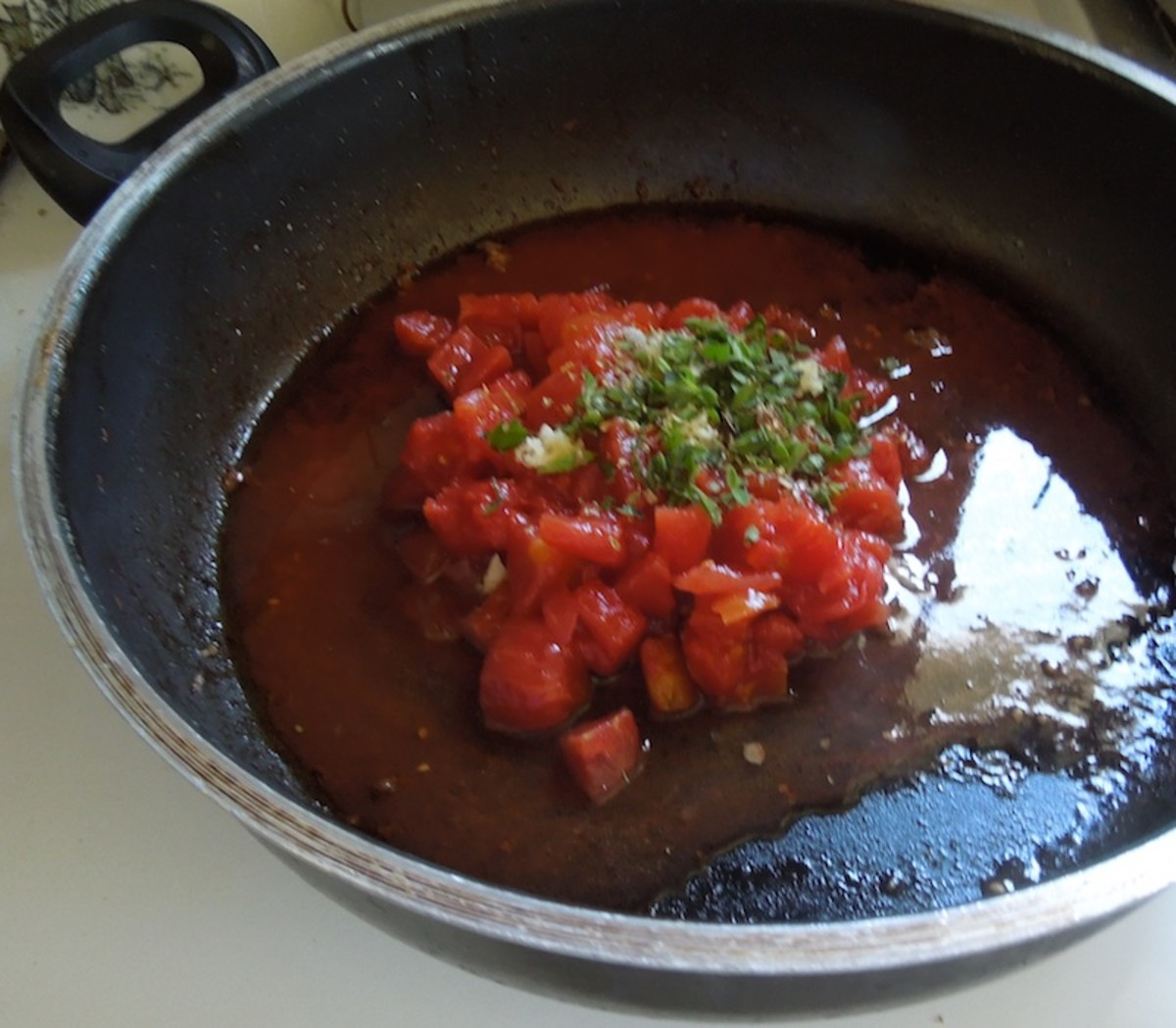 Put canned tomatoes and herbs in skillet with pan juices that remain.