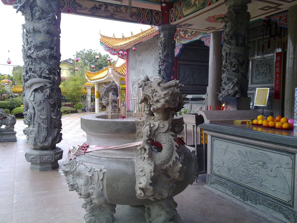 Large round urn filled with  joss sticks, in front of the temple