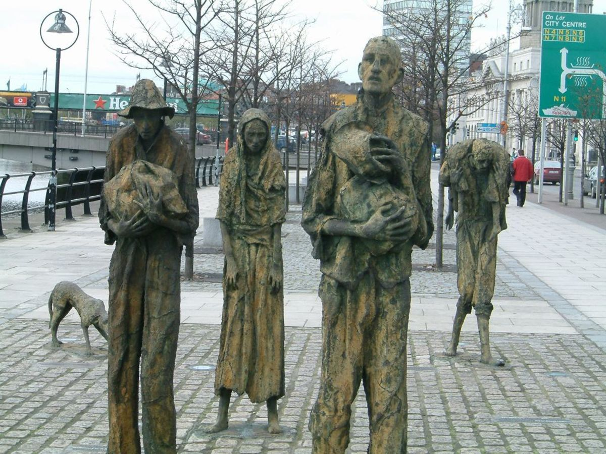 Customs House Quays, Dublin. Painfully thin sculptural figures, by artist Rowan Gillespie, stand as if walking towards the emigration ships on the Dublin Quayside.