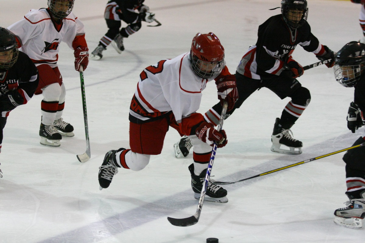Peewee youth hockey player learning to control puck while keeping his head up