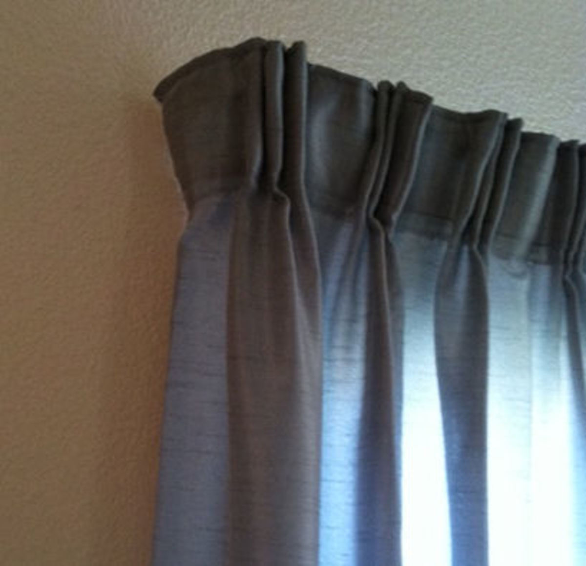 Wrapping the drapery around the end of the rod gives privacy, and keeps out light that will wake you in the mornings.