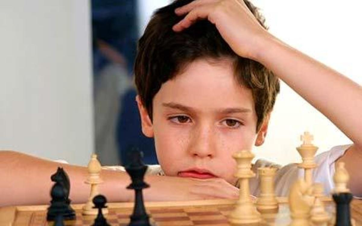 A boy using his critical thinking when playing chess