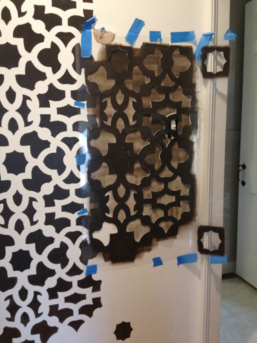 I needed to use a lot of tape to keep the stencil flush to the wall. Working around the door moulding was tricky.