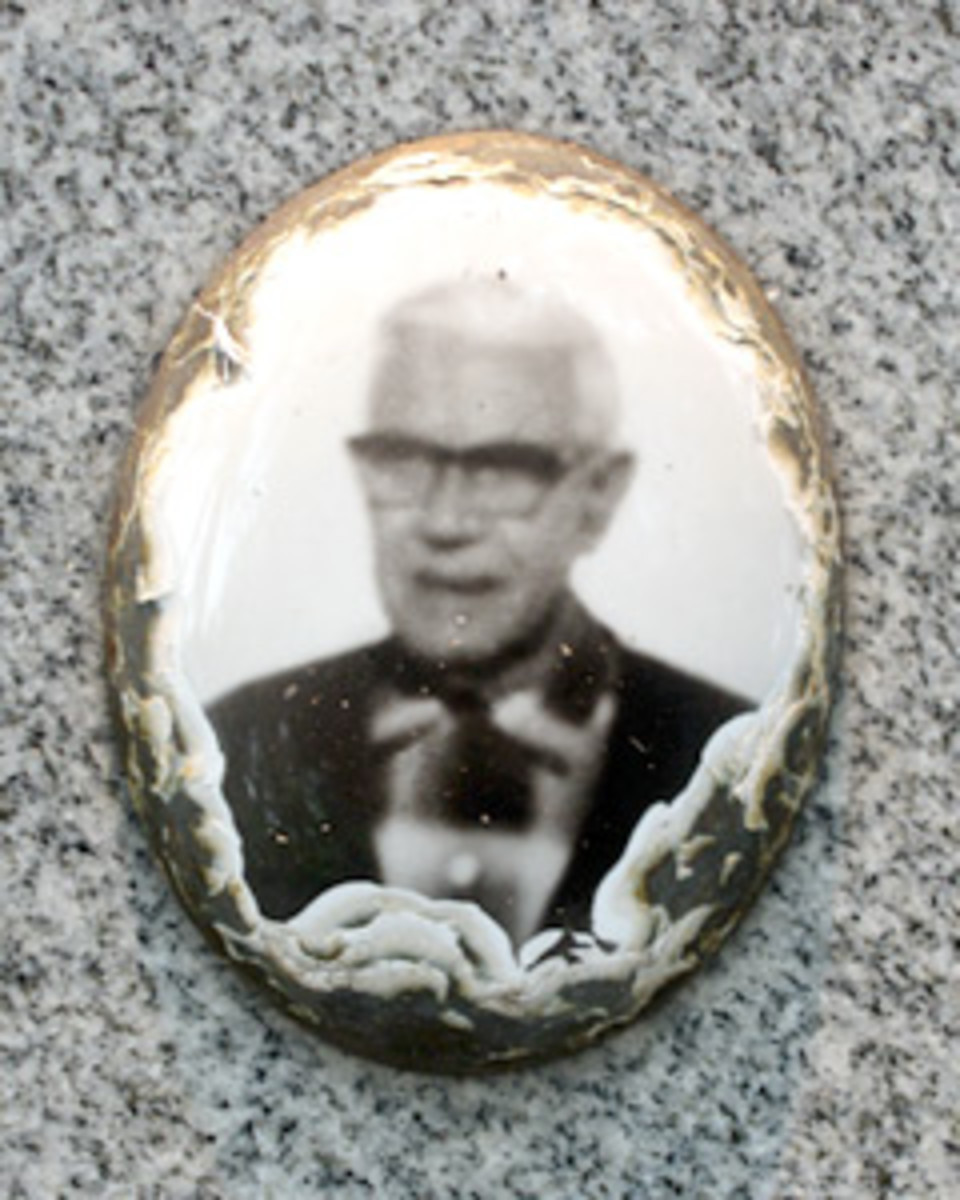 Very worn photo affixed to the front of a headstone