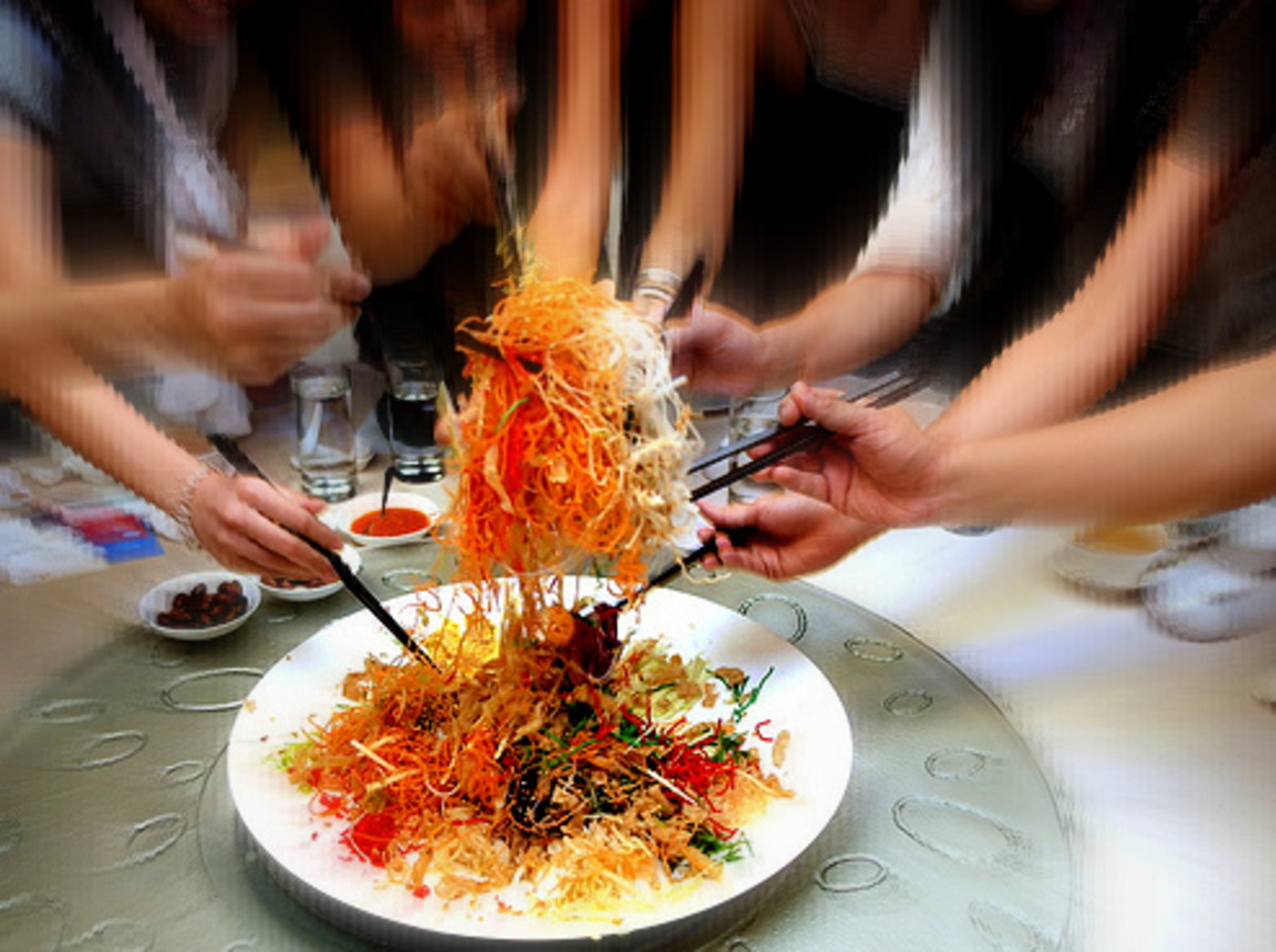 Serving yee sang: Using chopsticks, the ingredients are mixed and tossed as high as possible