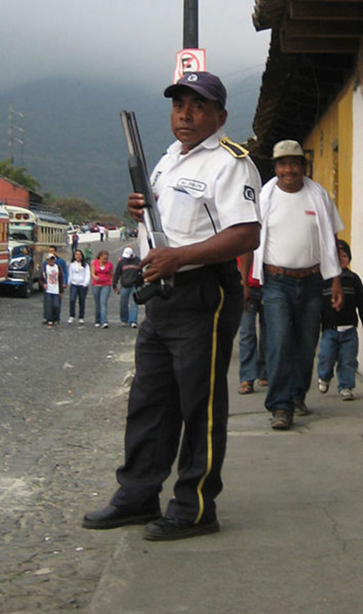 Private security guard with shotgun, guarding a bank in Antigua Guatemala.
