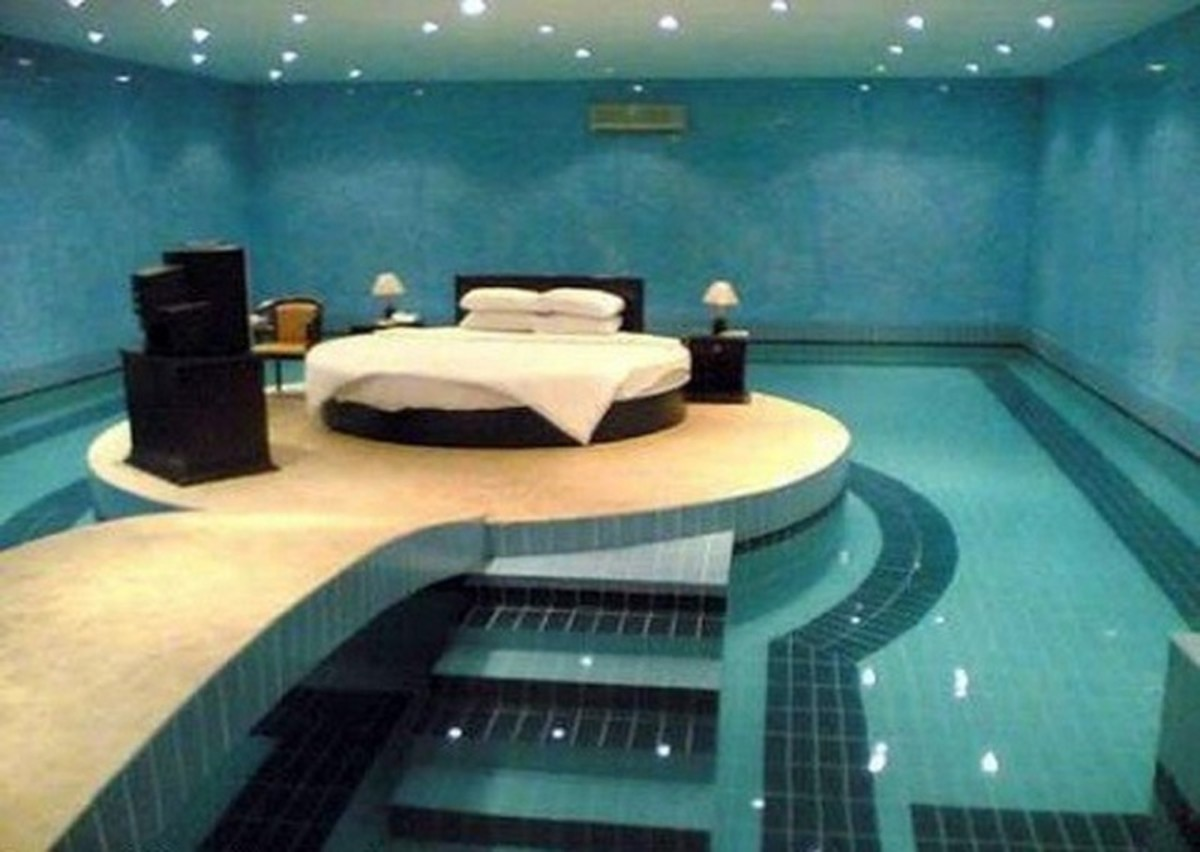 a round swimming pool surrounds the bed in this extreme bedroom suite complete with night stands and table lamps and a dresser
