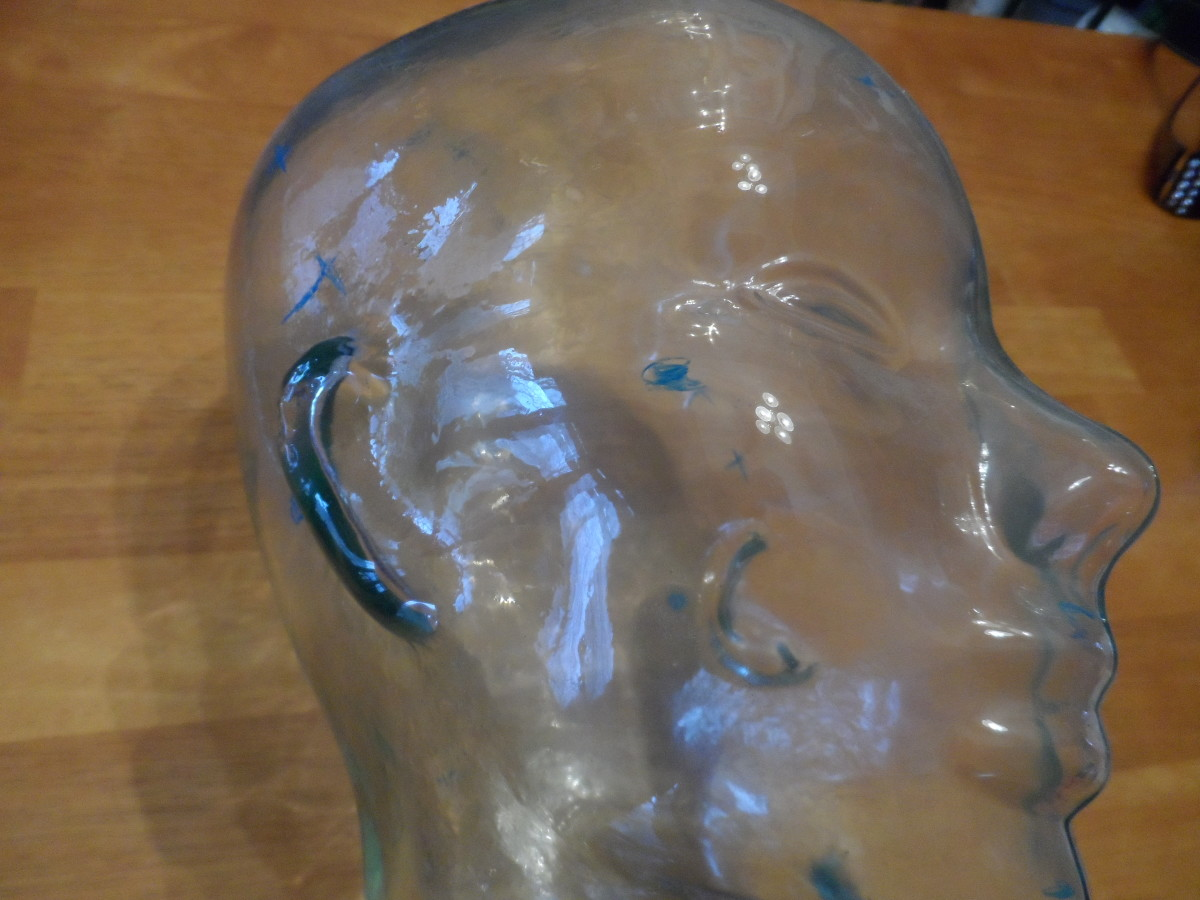 Glass face bust displaying areas wires are attached to a patient's head during a sleep study.