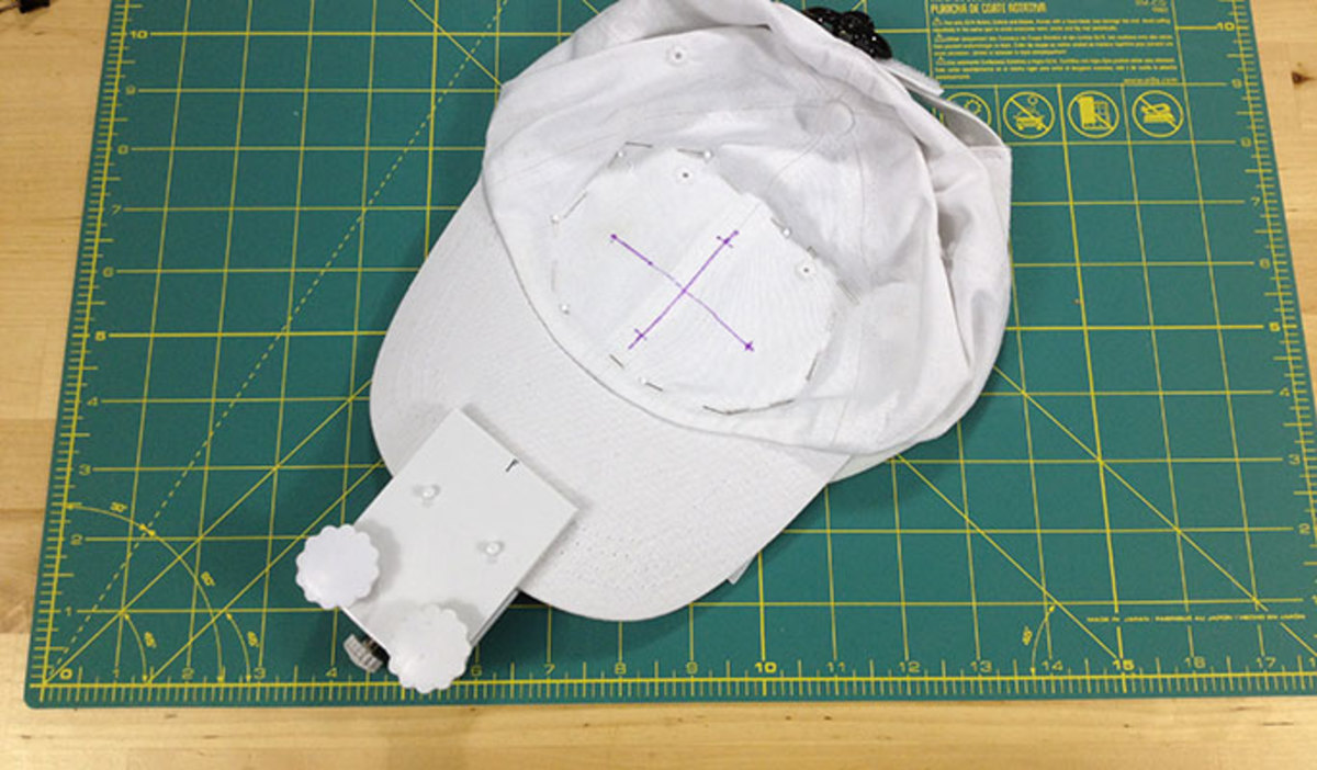 Remove the template gird. Press the cap down against the adhesive stabilizer starting in the middle and working out. The cap must be as flat and smooth as possible in the embroidery area. In this photo, I pinned the cap to the stabilizer around and o