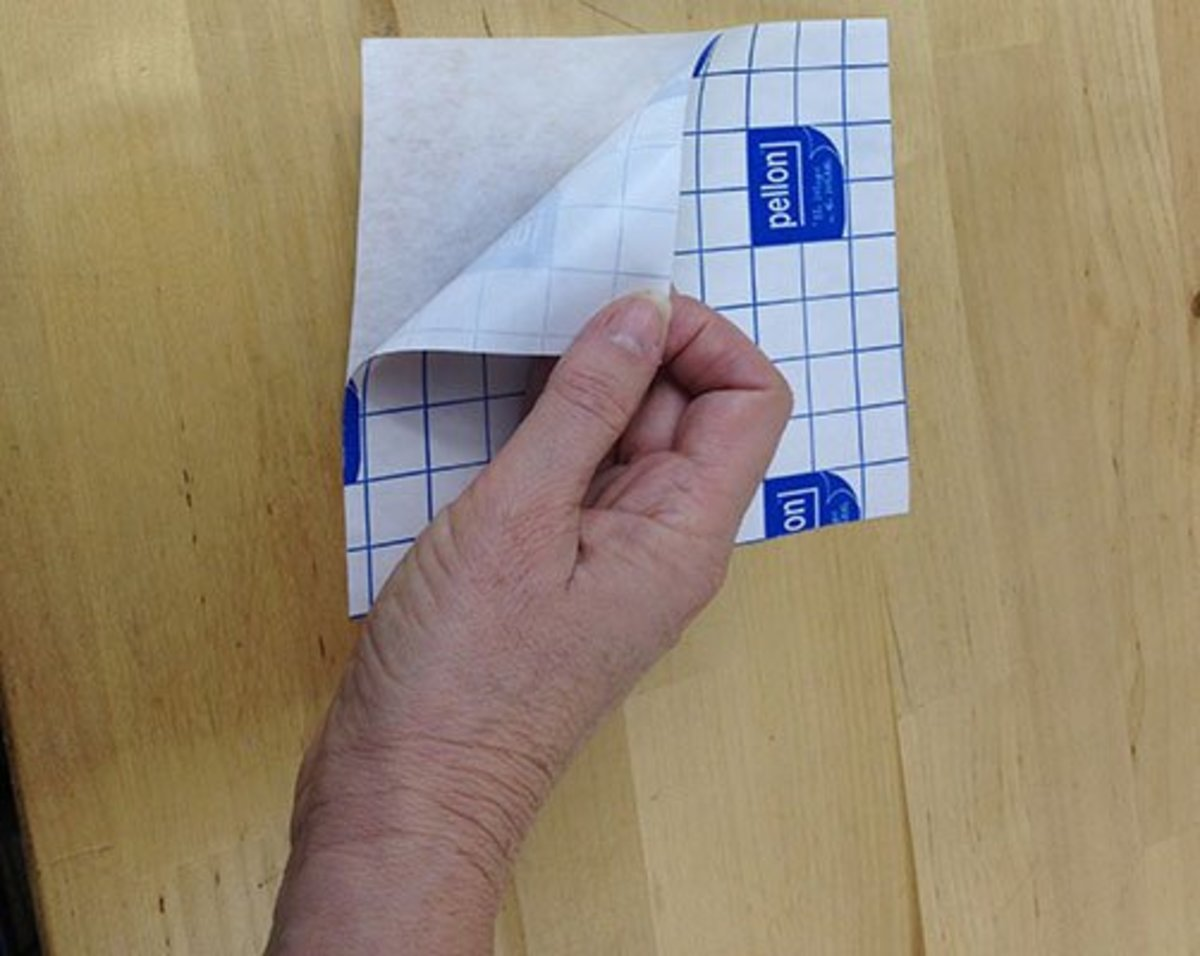 Cut a piece of adhesive stabilizer about an inch larger than the cap hoop. Pull the backing off.
