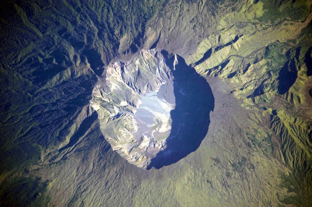 A detailed astronaut photograph depicting the summit caldera of the volcano Mount Tambora, Indonesia