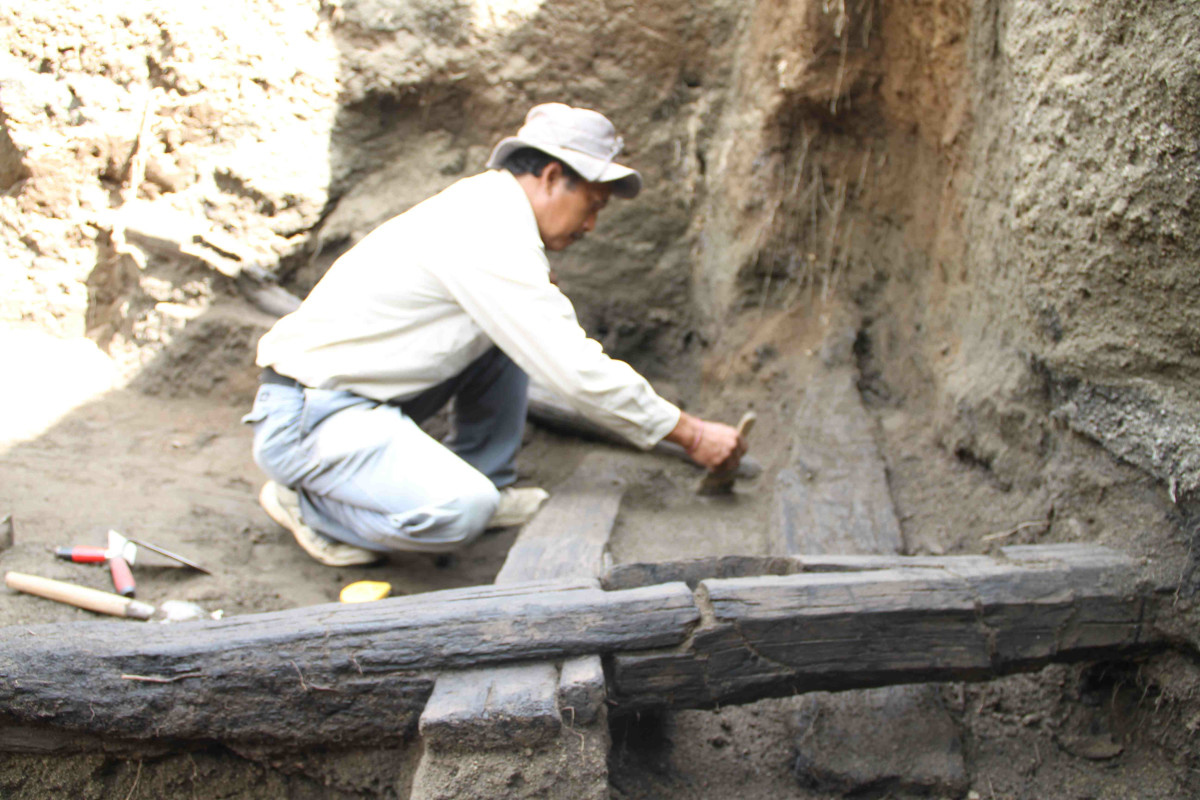 Excavating carbonized building beams (Photograph: Made Wita)