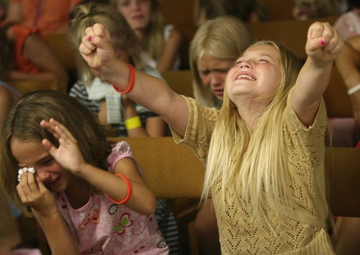 Lacey Johnson, 9, left, and Jasmine Anderson, 9, right, and Jaimie Brown, 10, in the center background, weep and raise their hands, after listening to a gospel presentation by Jason Mansur, a children's minister from Harvestime Church of Eau Claire,