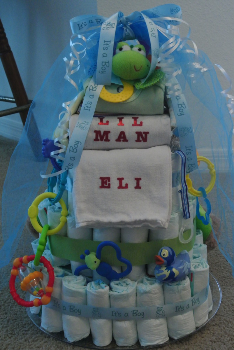 Cakes come in all colors, sizes and themes.  I wanted this cake to be blue and green and to be personalized with the little boy's name which I ironed on the burp cloth.  I had fun creating it and enjoyed giving it to the parents.