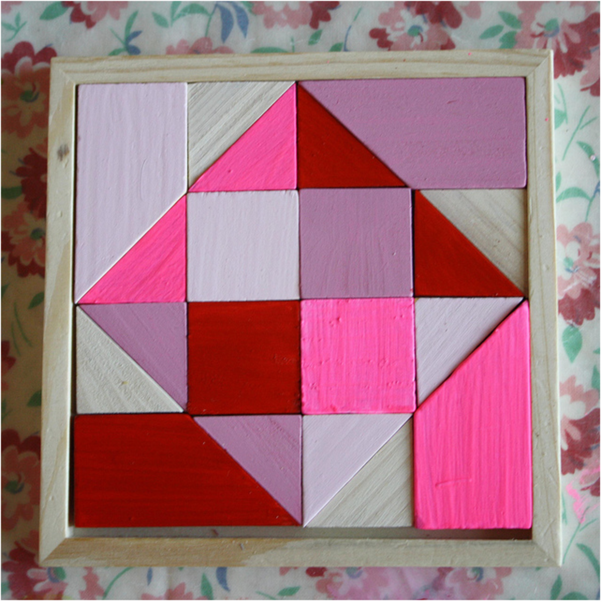 A puzzle like this can be made quite easily by starting with a square of thick wood and cutting it into different shaped pieces. You can then construct a wooden frame to hold all of the pieces together in the original square shape. Simple!