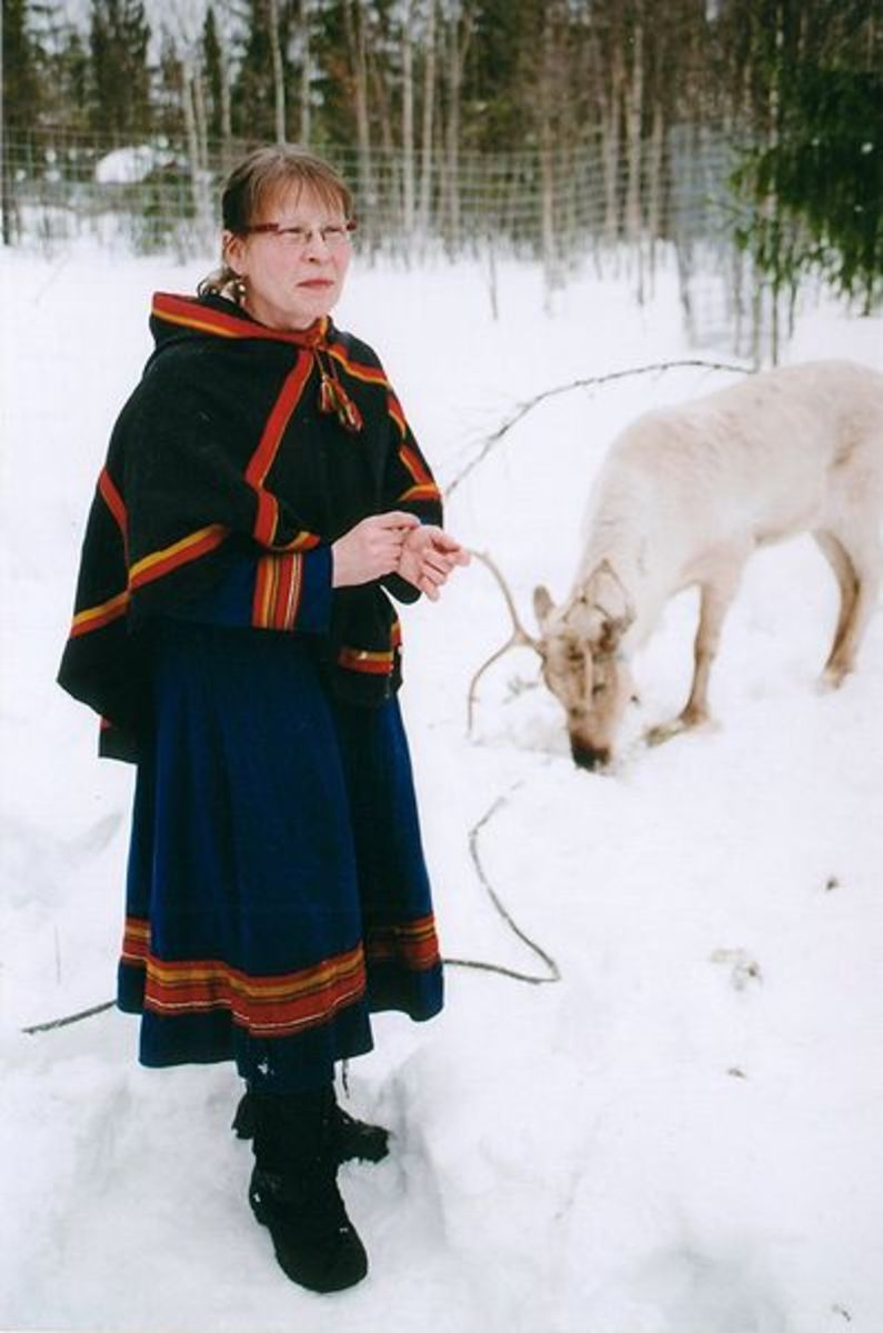 A Swedish Saami woman in traditional dress with a white reindeer. Photo by Anthony Randell.