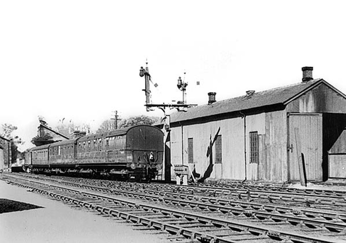 A train is pushed back out of Guisborough Station by an unidentified tank locomotive - heading east for Loftus - past Guisborough's small motive power depot, a sub-shed of Middlesbrough