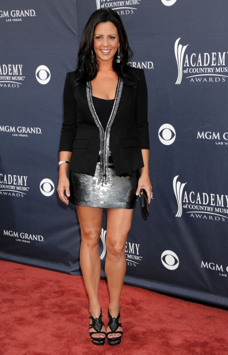 Sara Evans shows off her sexy legs in a short dress and high heels as she poses on the red carpet for the country music awards