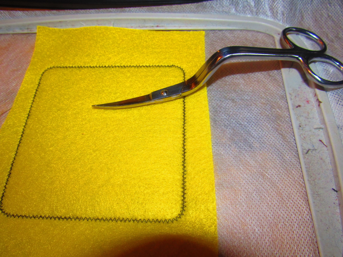 Once your fabric has been tacked down, use your sharpest scissors to trim around the patch.